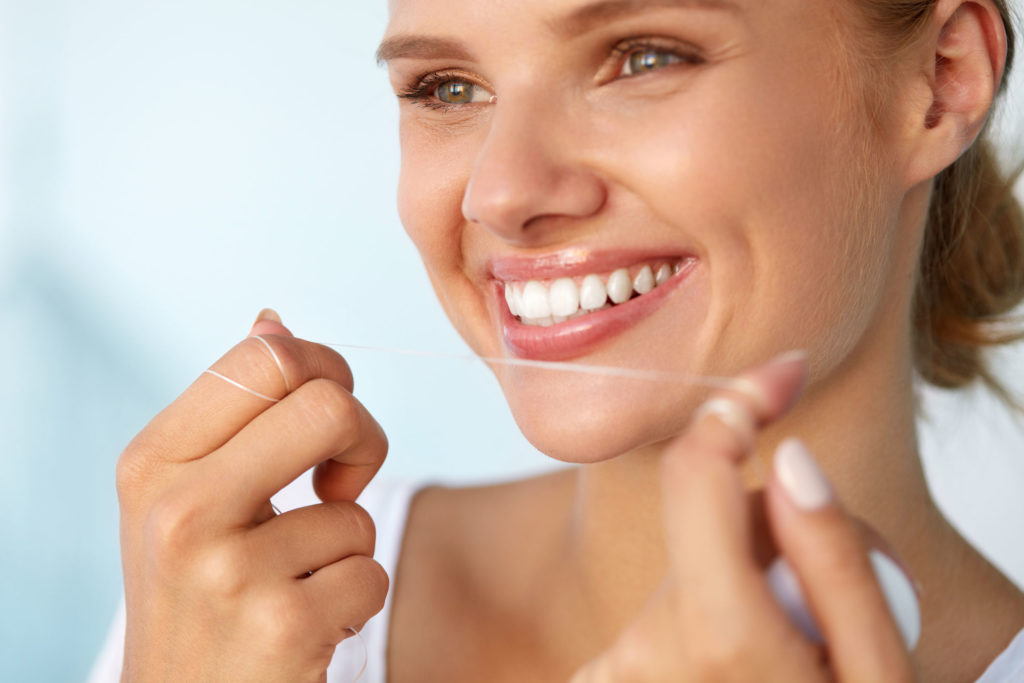 61732293 - dental hygiene. closeup of beautiful happy smiling woman with beauty face and perfect smile cleaning, flossing healthy white teeth using floss. oral health, tooth care concept. high resolution image