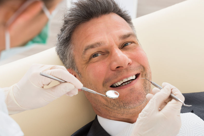 57754013 - happy mature man having dental check-up in clinic